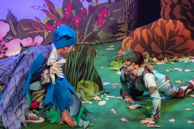 A man playing a Tūī approaches a woman playing a lizard, with leaves in her mouth