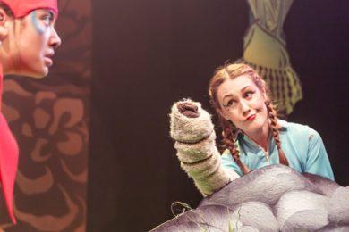 A woman playing a Takahē approaches a woman holding a huhu grub puppet