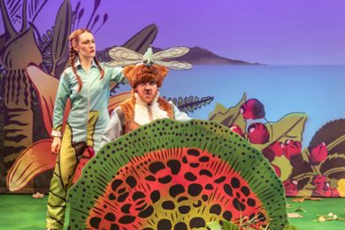 A female actor holds a dragonfly puppet over the head of a man playing a stoat